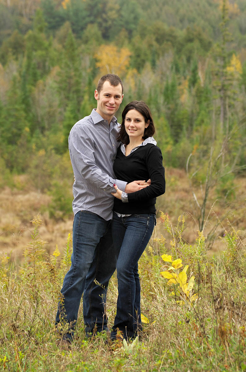 Couple embraces above Orange Corners Valley during Kawartha lakes engagement session