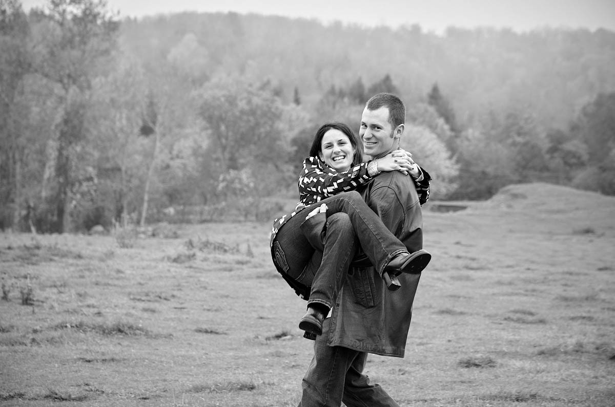 Young man carries girl in his arms through farm field