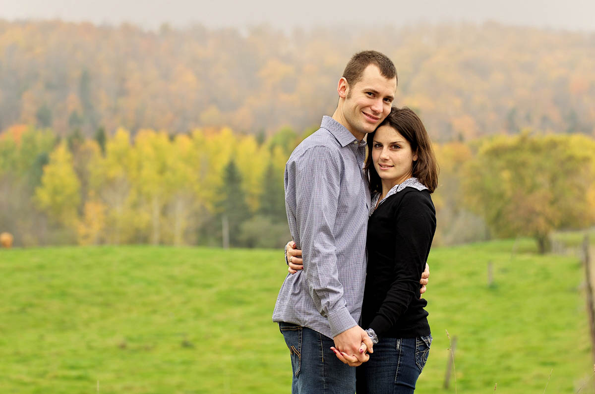 Young couple in farm field with fall colours and valley behind them during Omemee engagement session near Peterborough