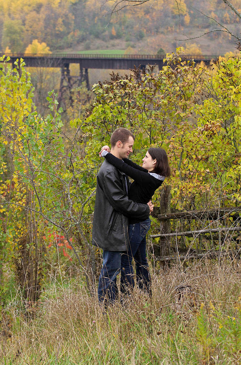 Young couple kisses near Orange Corners Bridge in Kawartha Lakes engagement photography session