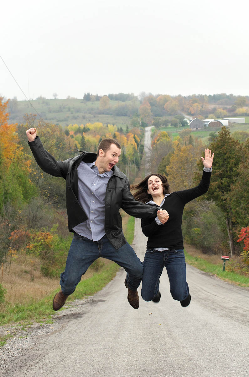 Couple jumps for joy on steep country road for country themed Peterborough engagement photography session