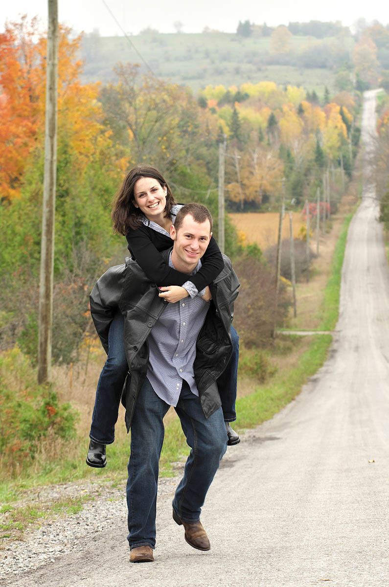 Piggybacking up a country road during Omemee country engagement session near Peterborough, Ontario