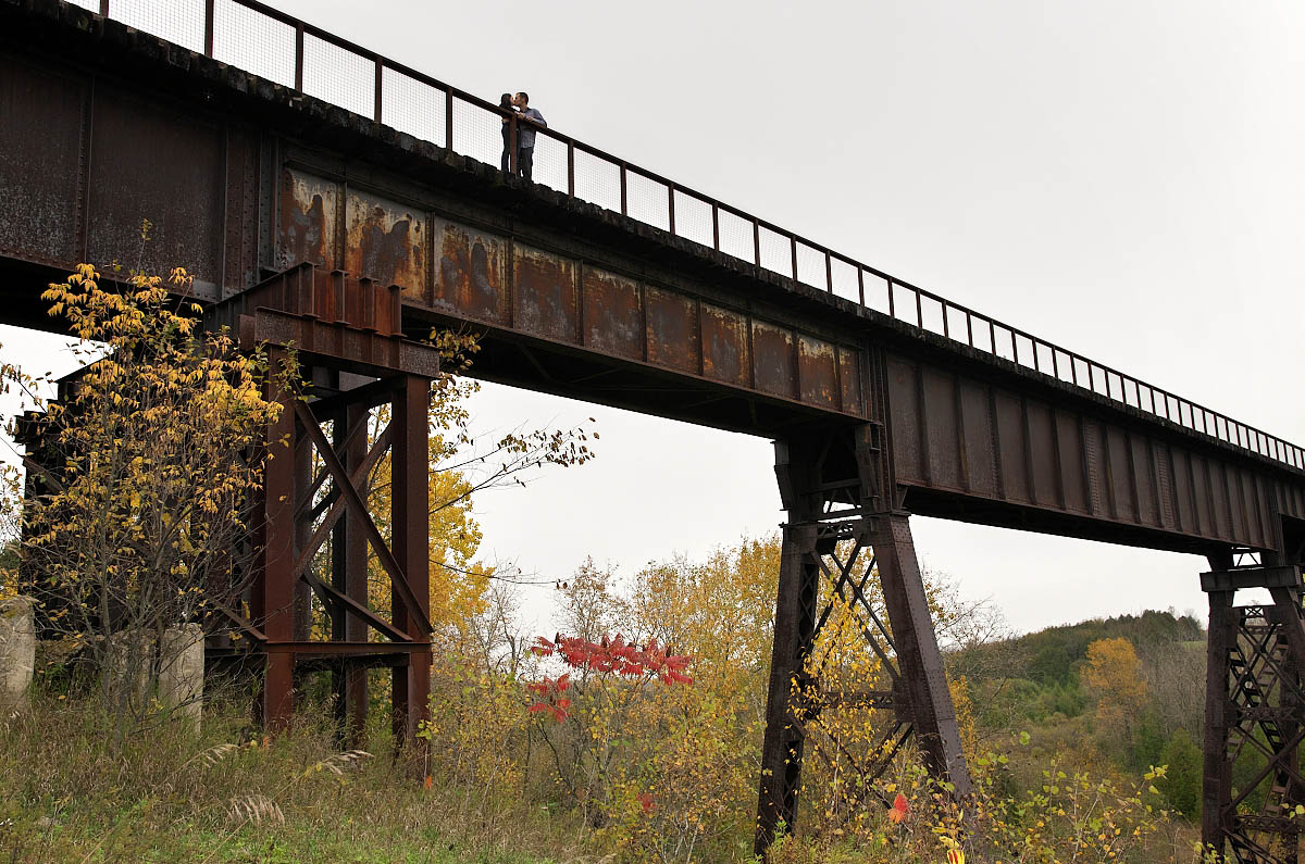 Young couple on Orange Corners Trestle Bridge during Omemee engagement photography session
