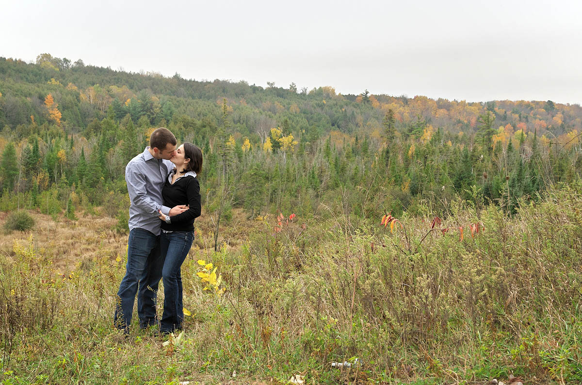 Young couple kissing at valley overlook in Orange Corners, Ontario
