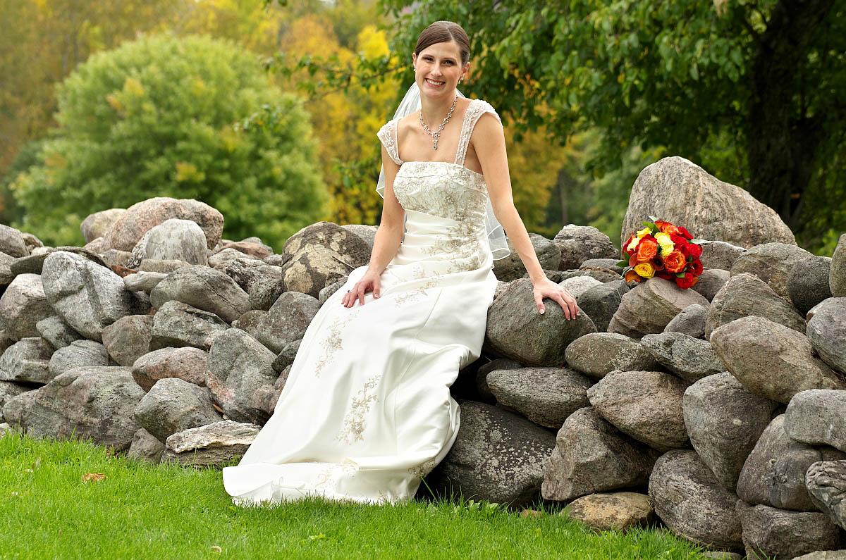 Beautiful bride sitting on old stone wall at EGanridge wedding near Bobcaygeon