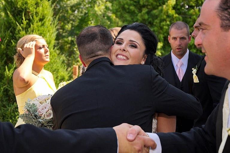 bride hugs groomsman after ceremony