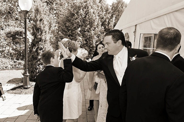 groom gives young guest a high five after wedding ceremony