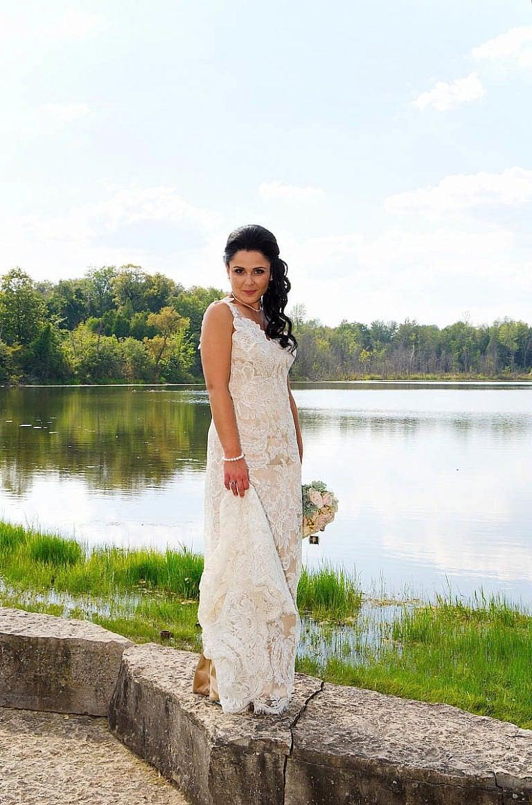 bride in front of pond at royal ambassador