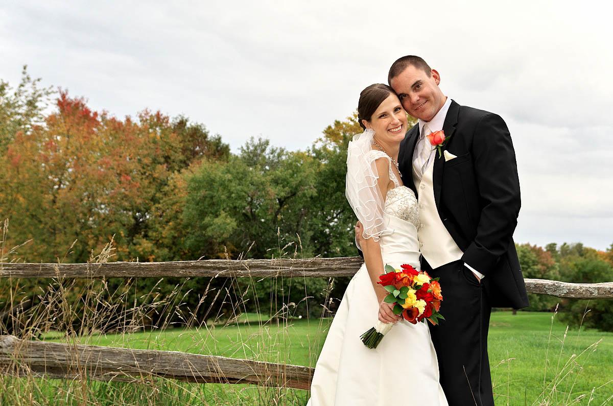 wedding couple by split rail fence at Eganridge Golf Club wedding
