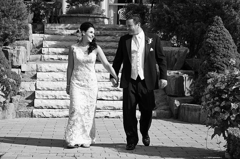 bride and groom strolling in garden at royal ambassador wedding