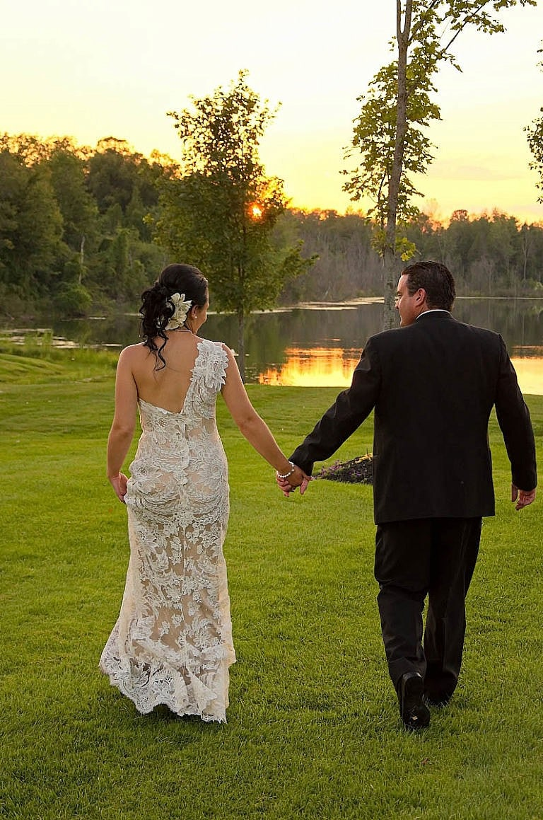 bride and groom stroll by pond at sunset at caledon wedding at Royal ambassador