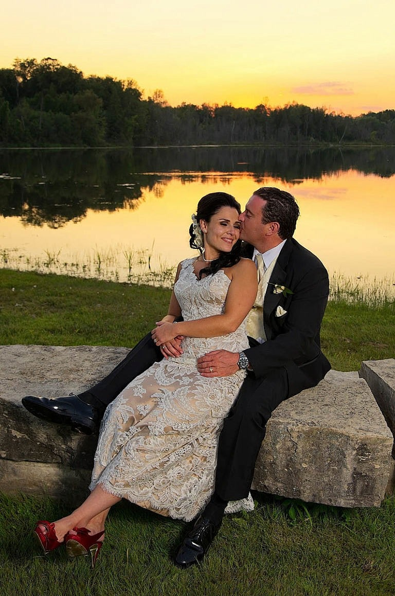 bride and groom on rocks in front of pond at sunset at caledon wedding at Royal ambassador