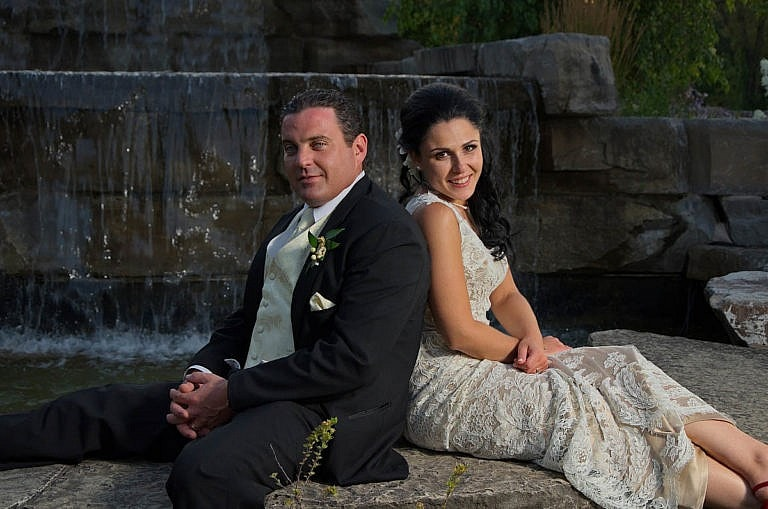 bride and groom by garden waterfall at Royal Ambassador wedding