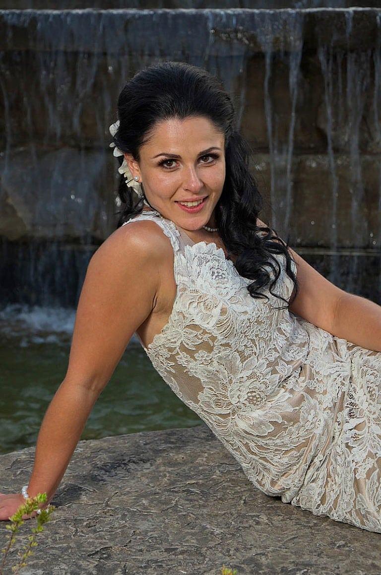 bride by garden waterfall at Royal Ambassador wedding