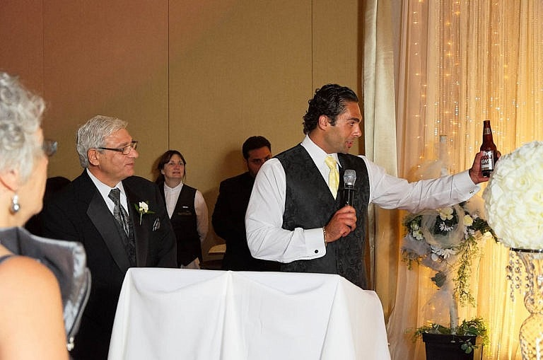 groomsman makes a toast at wedding reception