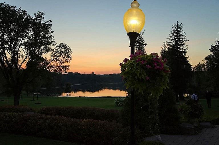 Lamp post, garden, and pond at dusk at Royal Ambassador