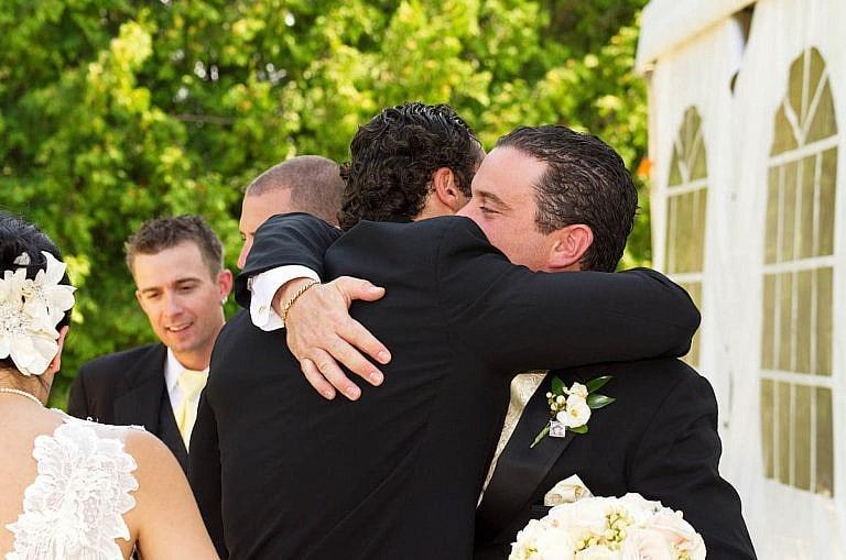Groom hugs groomsman at Caledon wedding at Royal Ambassador