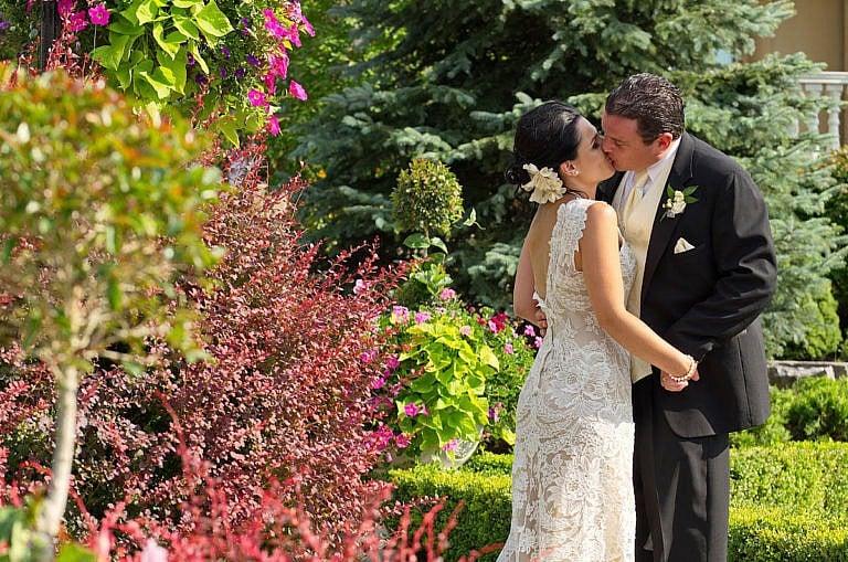 Wedding couple kisses in lush gardens a Caledon wedding at The Royal Ambassador