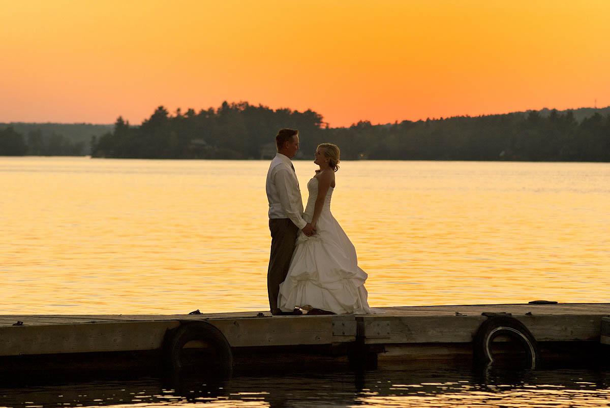 wedding couple at sunset on dock at irwin inn on stoney lake