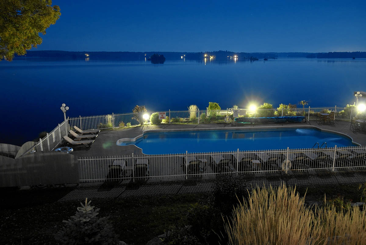 viamede's outdoor pool lit up a night on stoney lake