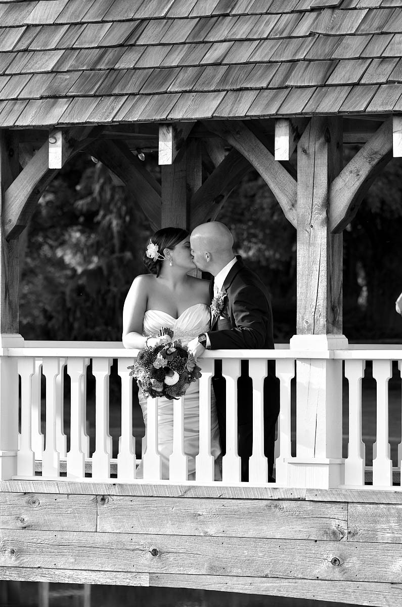 covered bridge wedding kiss in black and white