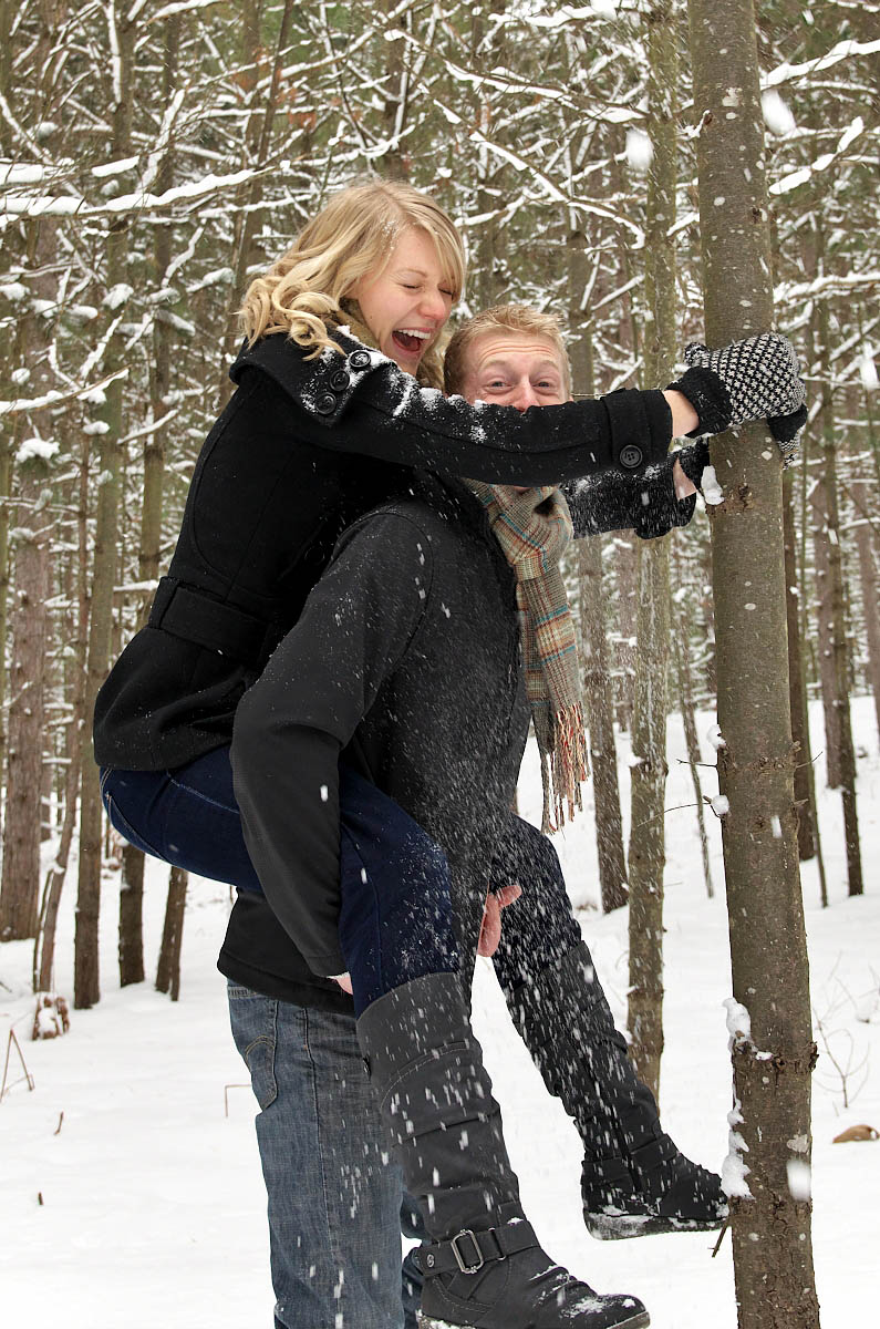 shaking snow covered tree engagement photo