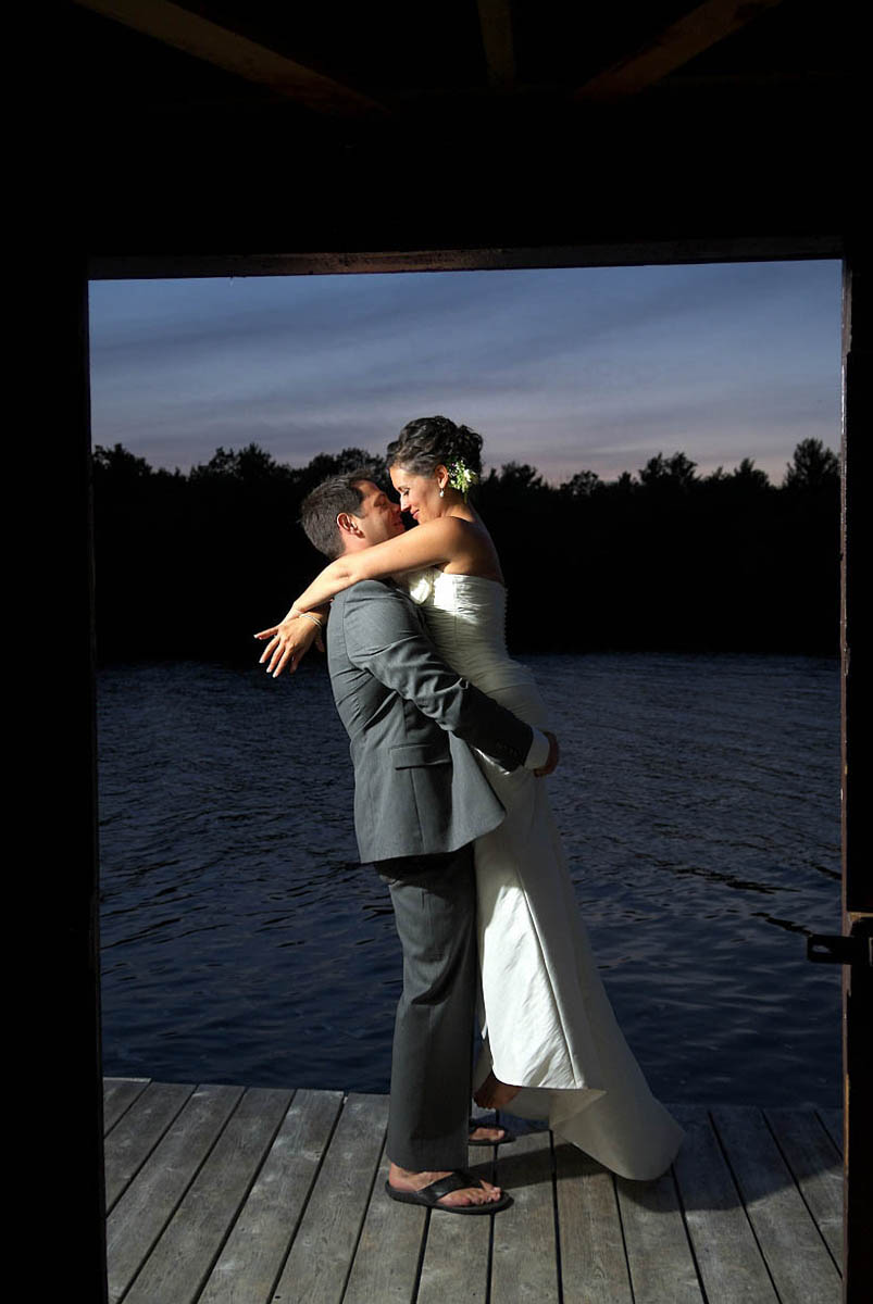 At dusk, groom lifts his bride in his arms outside boathose on Stoney Lake