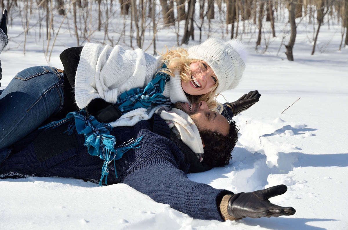 happy couple frolicks in snow during engagement photography session on bruce trail, at top of blue mountain in collingwood