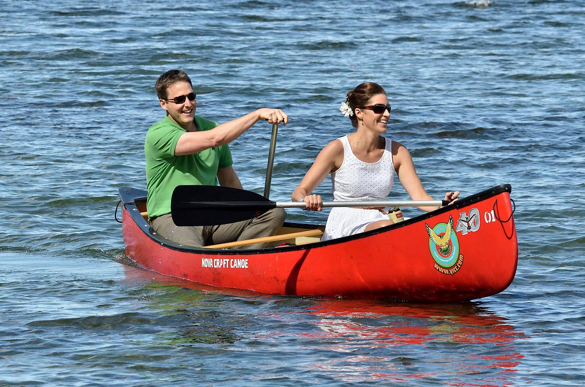 bride and groom kissing in red canoe at summer camp wedding