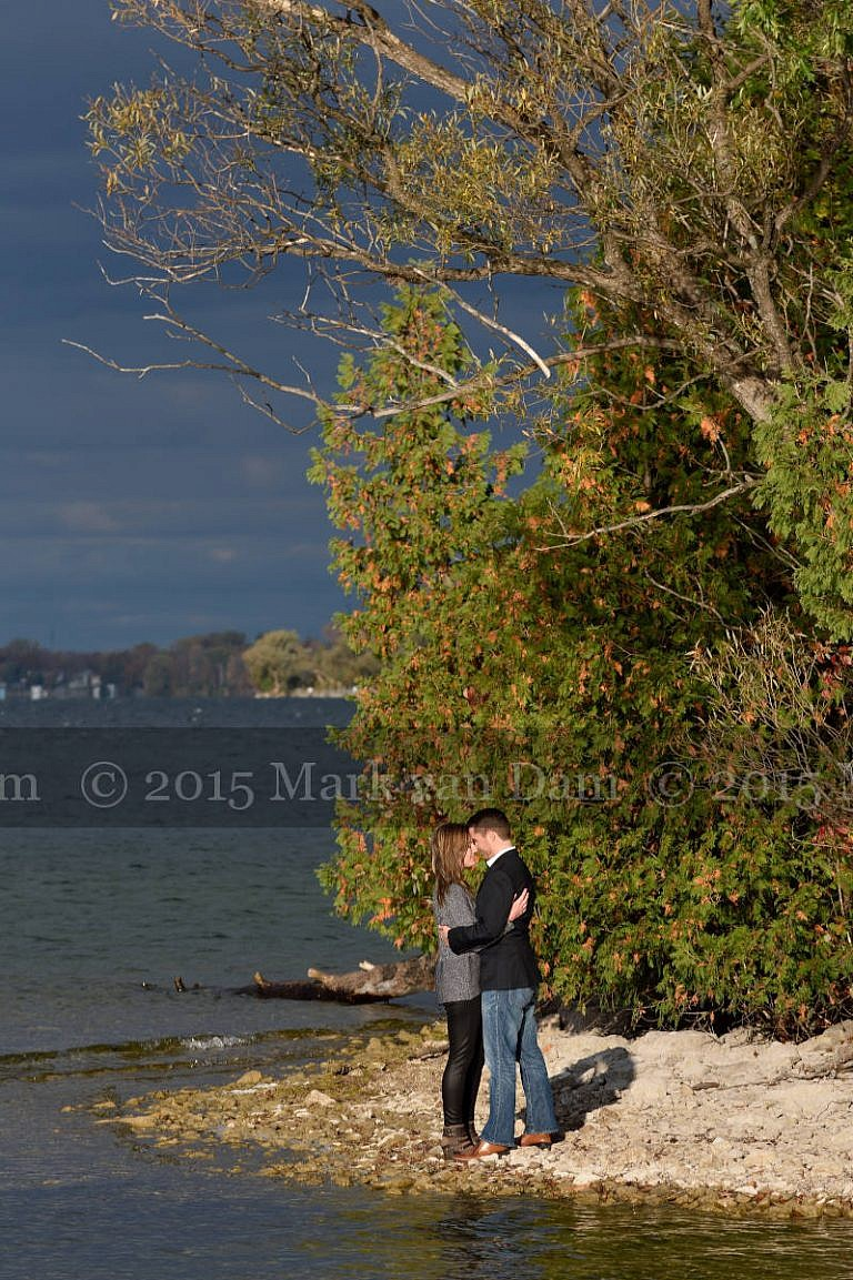 Couple kissing on shores of Lake Couchiching at Orillia engagement session at Leacock Museum
