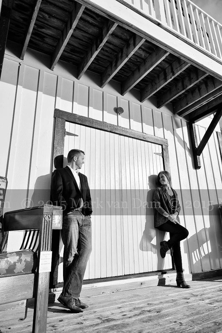 Stylish couple leans against boathouse door at Leacock Museum engagement photography session