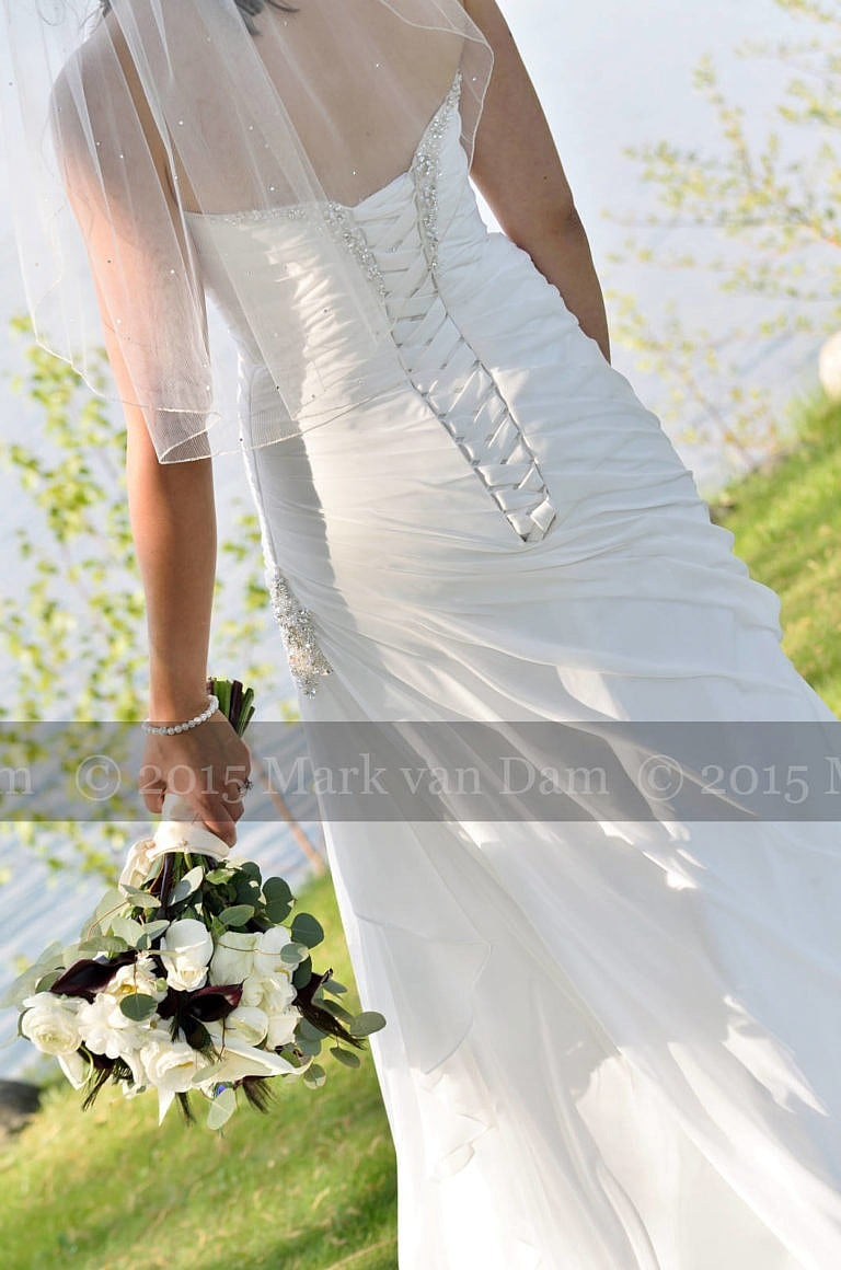Detail of back of dress and bouquet of Beautiful bride by Georgian Bay at Living Waters Resort at The Bear Estate at Cranberry Resort