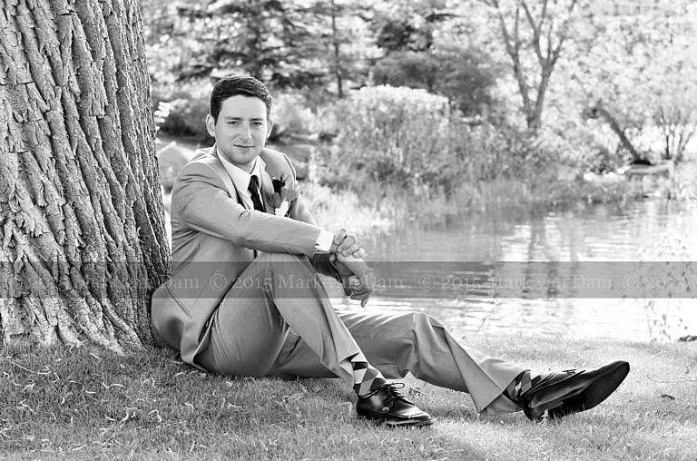 Handsome groom leans against willow tree by Georgian Bay at Living Waters Resort at The Bear Estate at Cranberry Resort