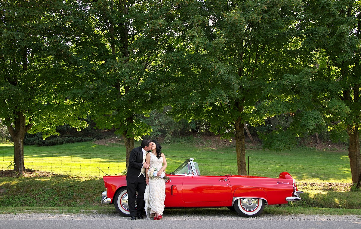 bride and groom kiss by cherry red classic car at royal ambassador wedding in caledon ontario