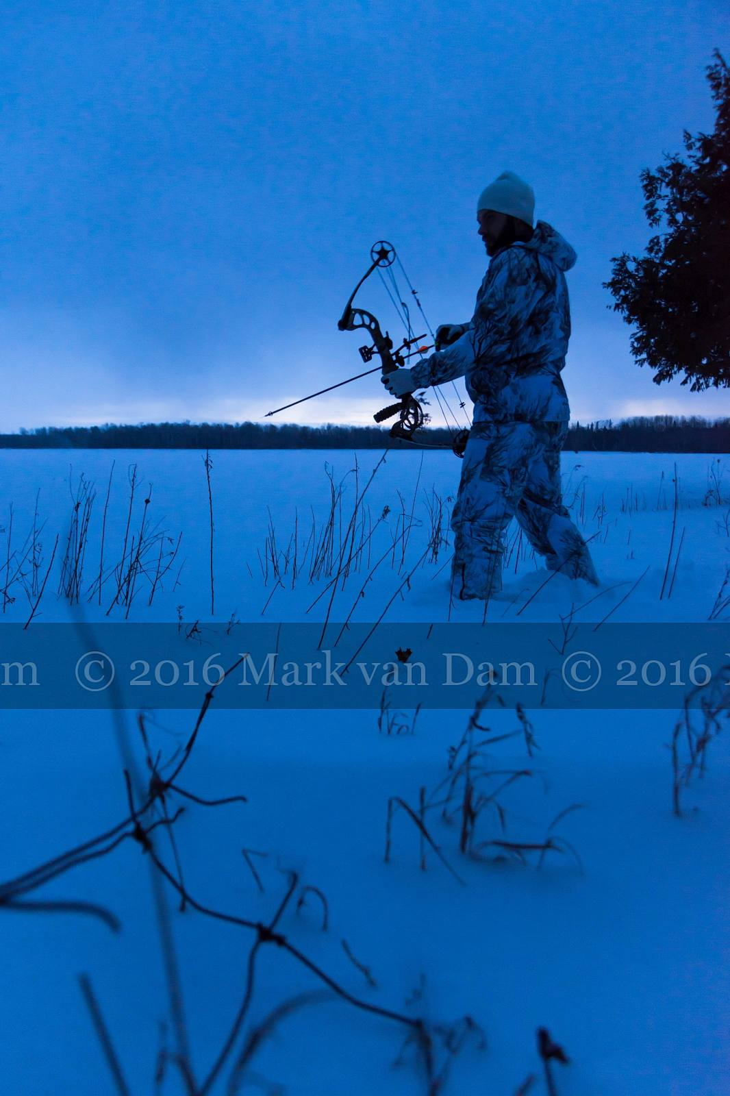 twilight silhouette of compound bow hunter in winter