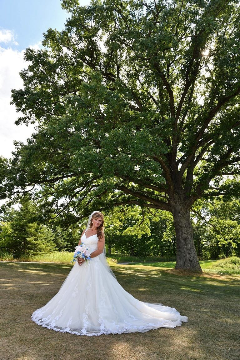 Bride beneath large tree at The Club at Bond Head