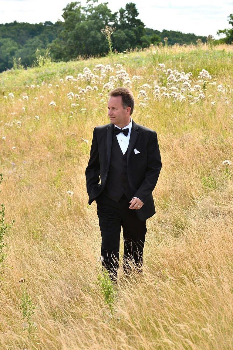 Groom walking through meadow at Bond Head wedding