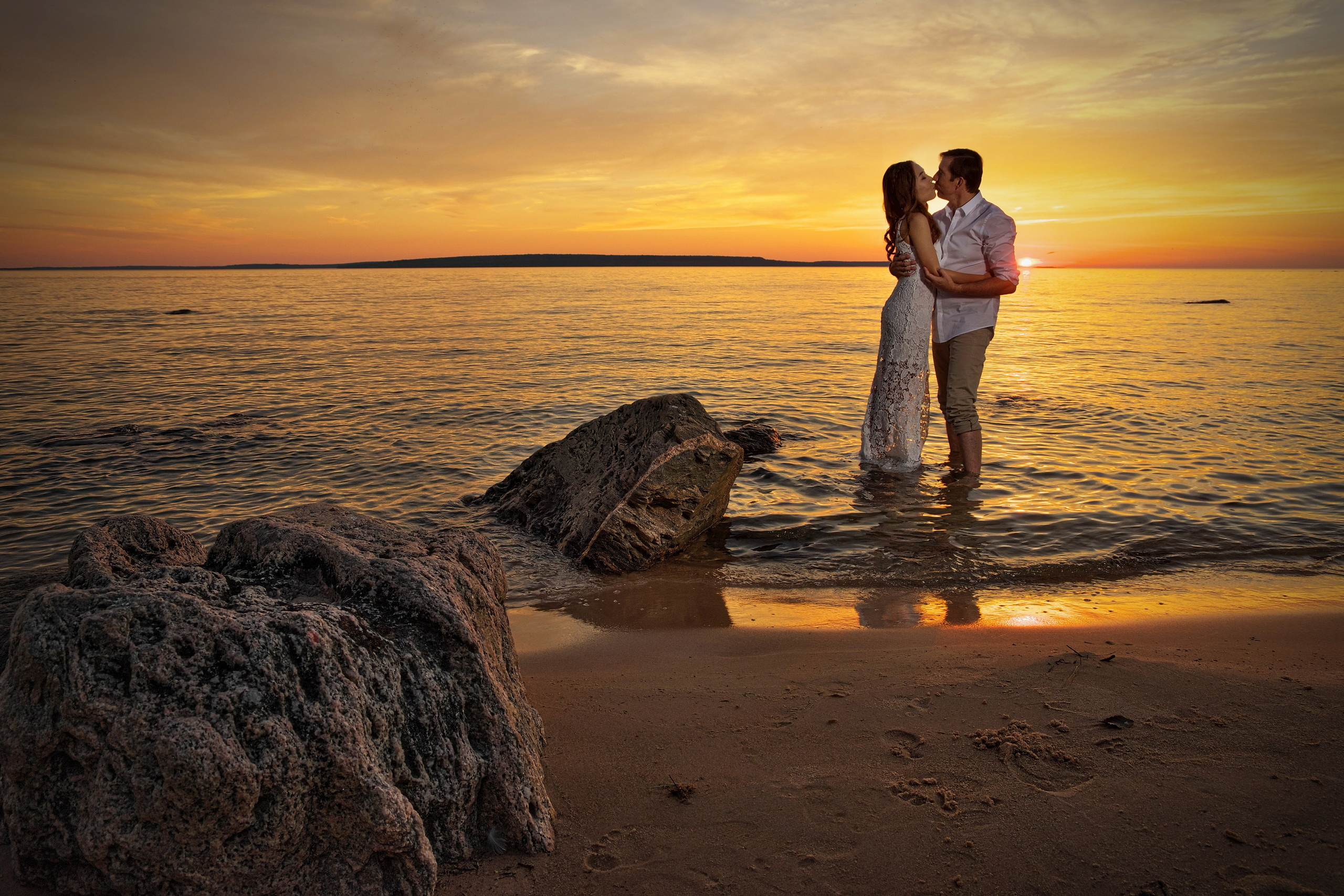 young couple kissing at sunset at awenda provincial park standing in water