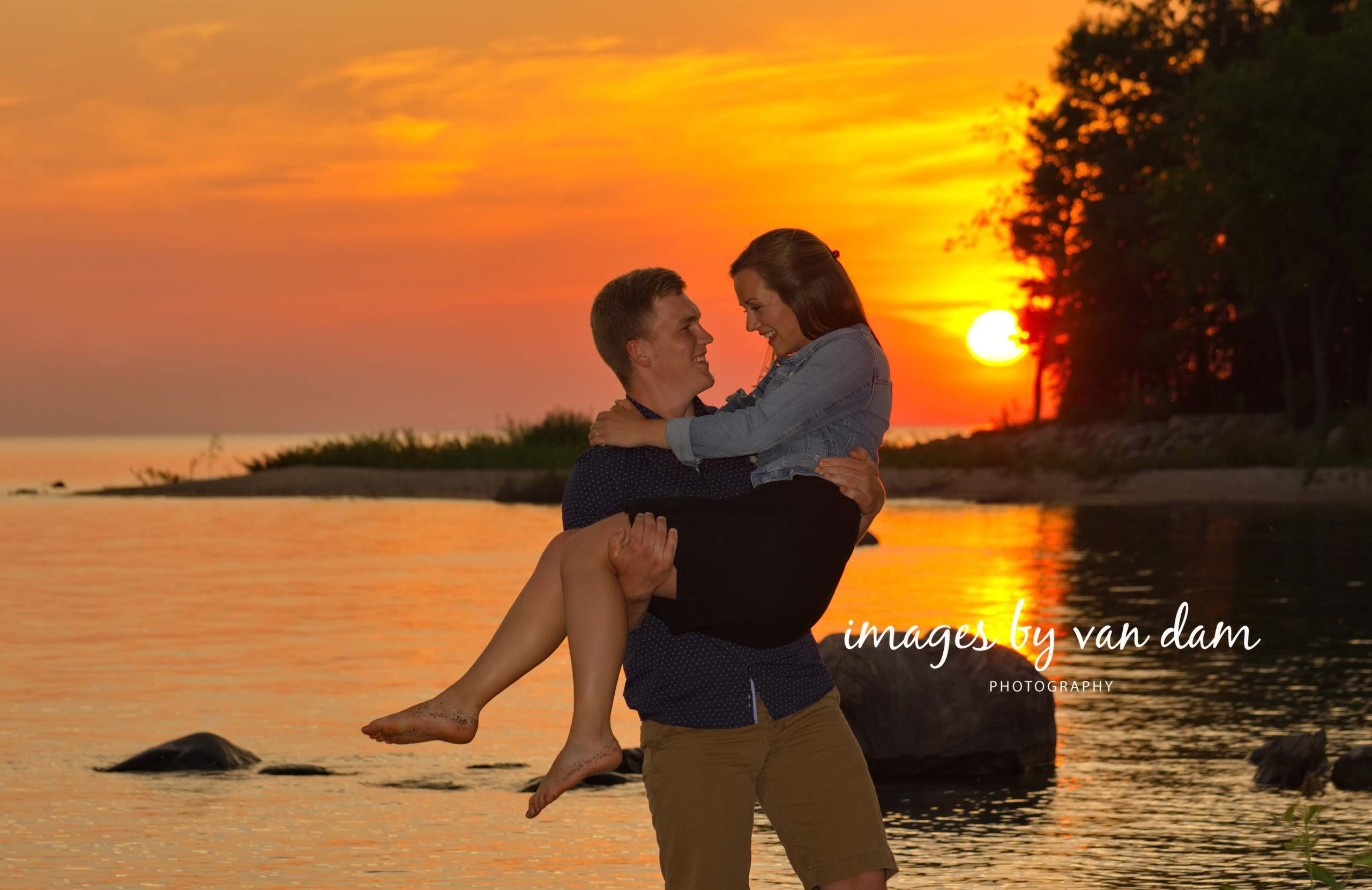 Young man lifts woman in his arm with dramatic sunset behind
