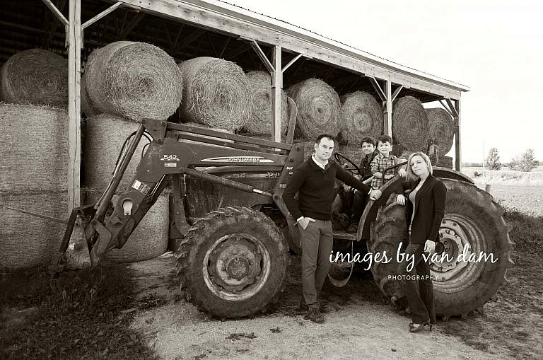 Young Family Poses in front of Tractor and hay bales stayner photographer barrie photographer family portraits wasaga photographer collingwood photographer