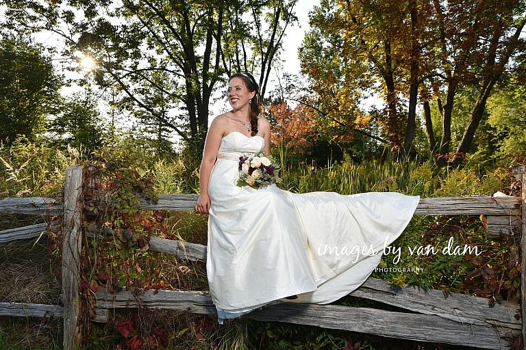 Beautiful Bride Sits on Split Rail Fence