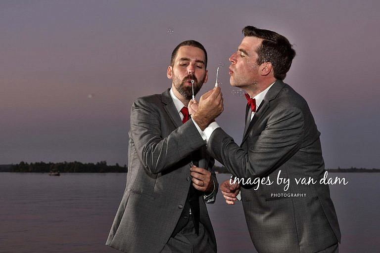 Two Grooms Blow Bubbles on Dock at Dusk