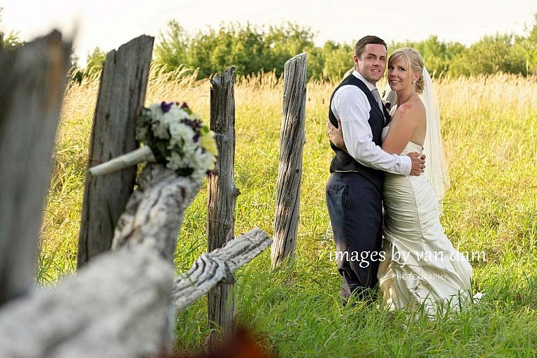bride and groom at abandoned orchard with bouquet on split rail fence near Lora Bay wedding