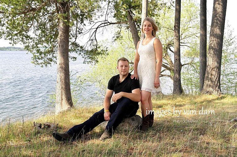 Couple by lake in Bridgenorth, Ontario at country themed engagement session