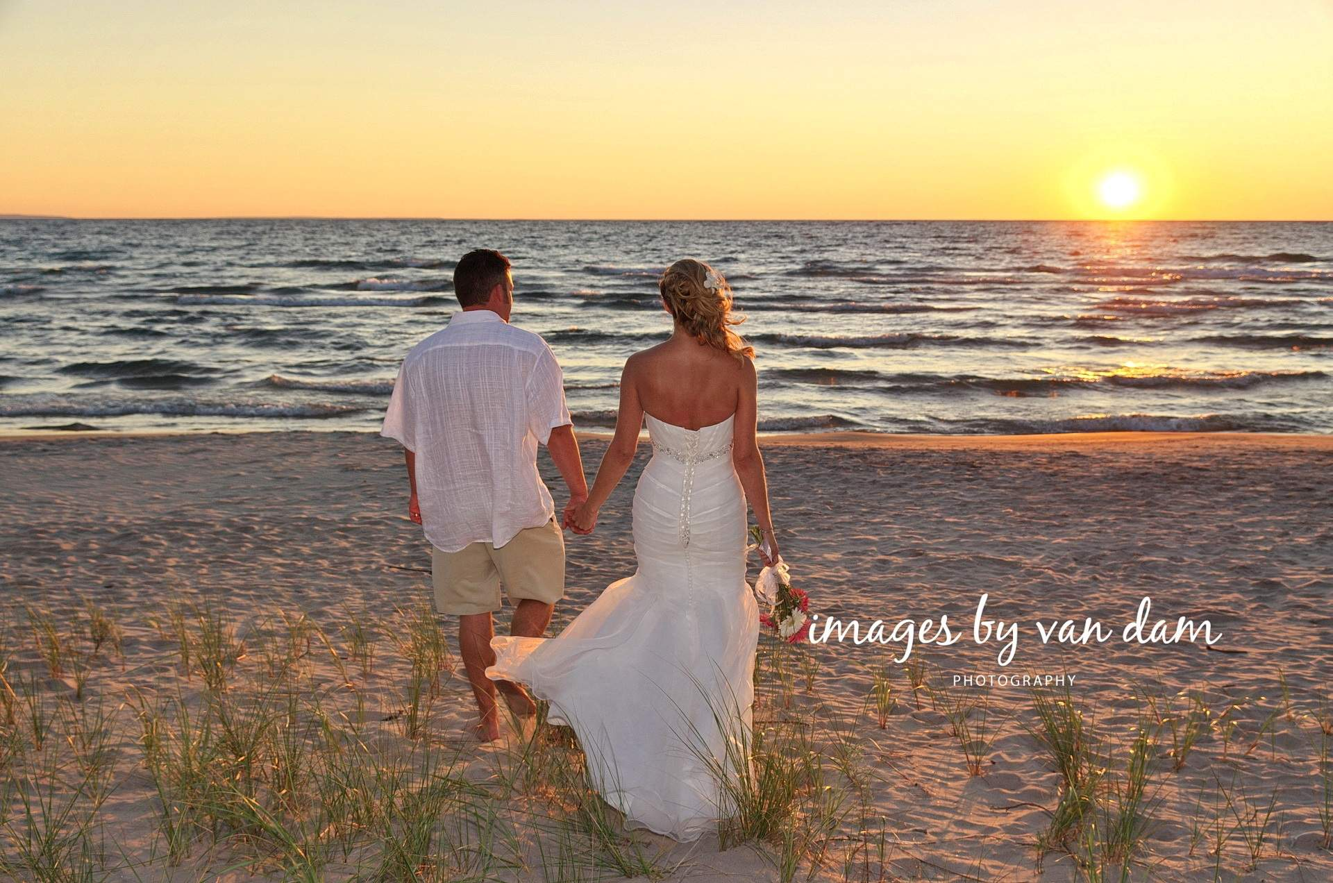 barrie photographer wedding couple walking hand in hand towards epic sunset at wasaga beach wedding