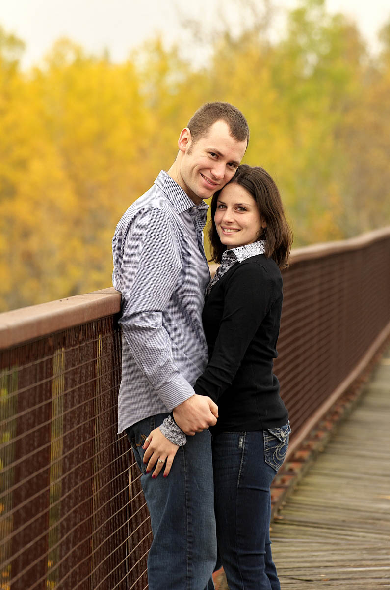Young couple on trestle bridge at Orange corners engagement session near Omemee, Lindsay, and Peterborough