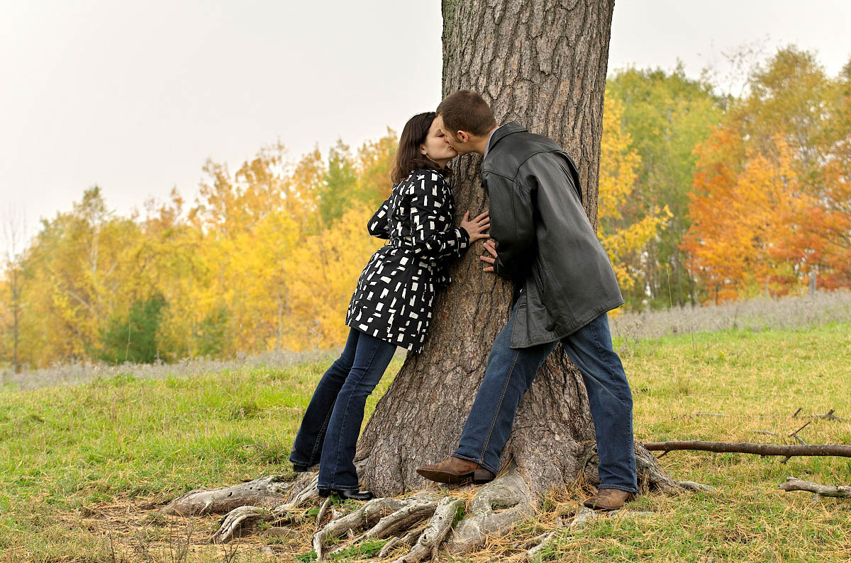 Young couple kisses by lone tree in farm field at country engagement session in Peterborough, Ontario