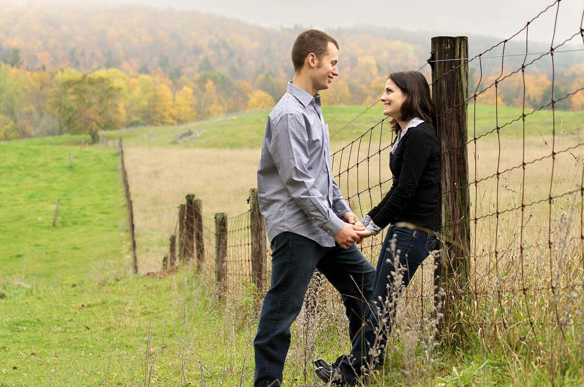 Young couple in farm field by fence at country themed engagement session