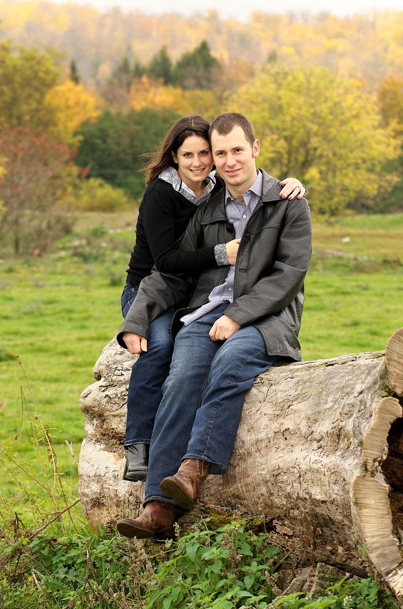 Young couple snuggles on boulder at country themed engagement session on farm