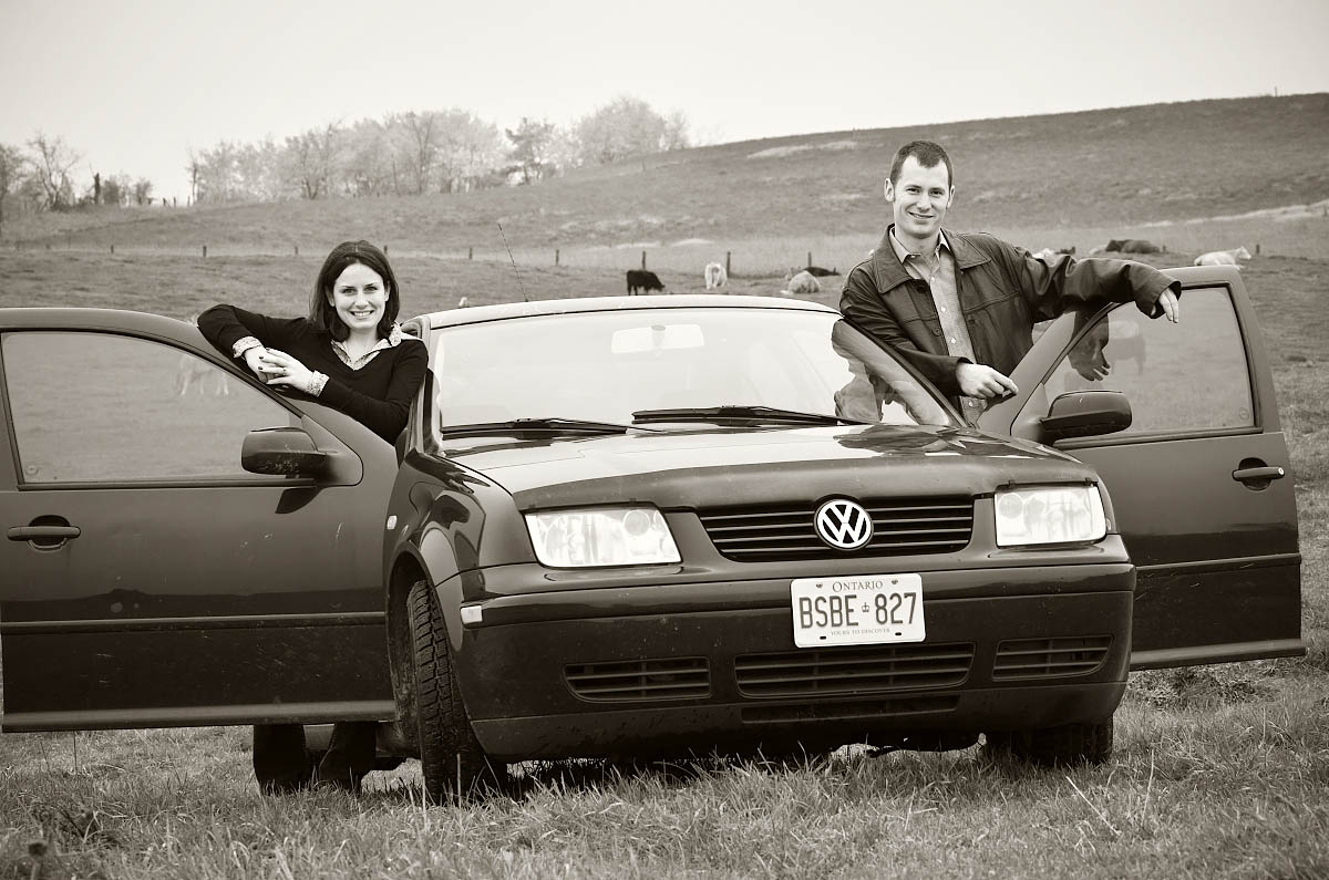 Young couple pose with their first car in farm field